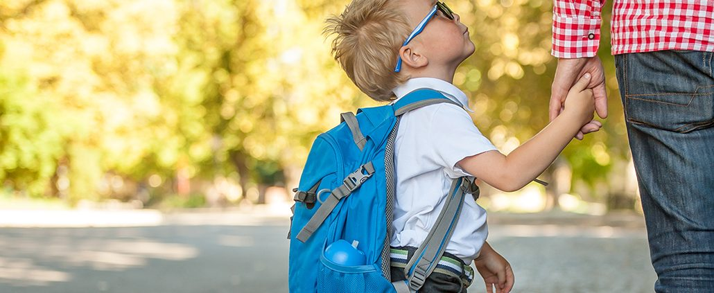 Young boy looking up at adult as they wait for school bus
